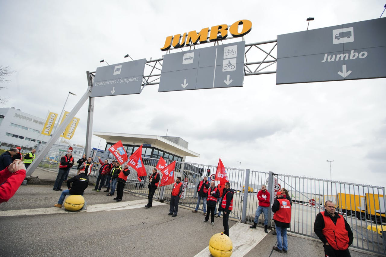 Stakende werknemers van Jumbo-distributiecentra blokkeren de toegangspoort bij de vestiging in Woerden.