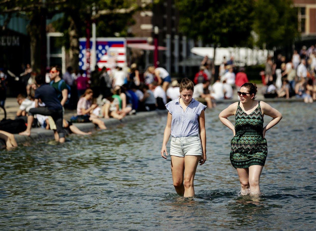 Mensen zoeken verkoeling in de vijver op het Museumplein het centrum van Amsterdam