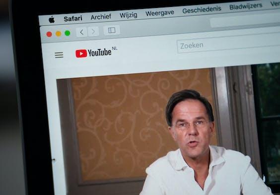 Een laptopscherm met premier Mark Rutte en minister Hugo de Jonge van Volksgezondheid, Welzijn en Sport (CDA) die vragen beantwoorden over het coronavirus tijdens een livesessie via Facebook en YouTube.