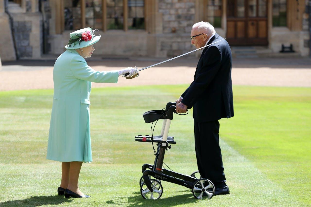 Koningin Elizabeth slaat Tom Moore tot ridder met het zwaard van haar vader.