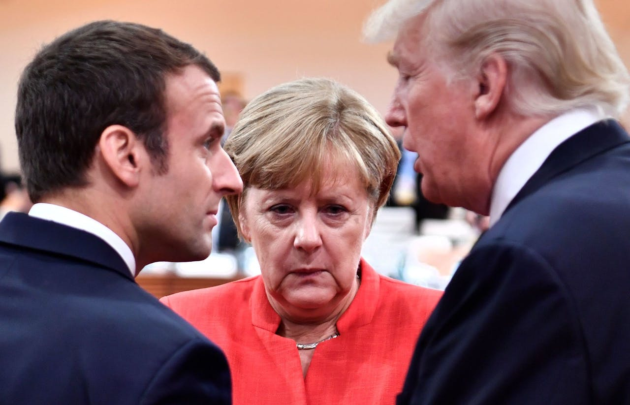 """2017-07-07 13:48:28 (FILES) In this file photo taken on July 07, 2017 (L-R) French President Emmanuel Macron, German Chancellor Angela Merkel and US President Donald Trump confer at the start of the first working session of the G20 meeting in Hamburg, northern Germany.US President Donald Trump on March 27, 2018 spoke with European leaders about working together to counter China's alleged unfair trade practices, the White House said. The move comes as Washington and the European Union are at loggerheads over Trump's decision earlier this month to slap steep tariffs on steel and aluminum imports.Trump and German Chancellor Angela Merkel """"discussed joining forces to counter China's unfair economic practices and illegal acquisition of intellectual property,"""" the White House said in a statement. / AFP PHOTO / John MACDOUGALL"""