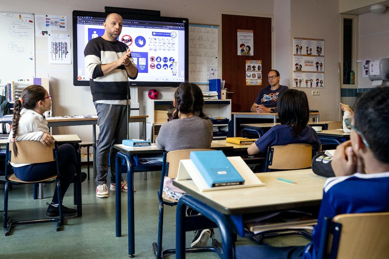 Een leerkracht legt basisschoolleerlingen uit hoe de handen te wassen.