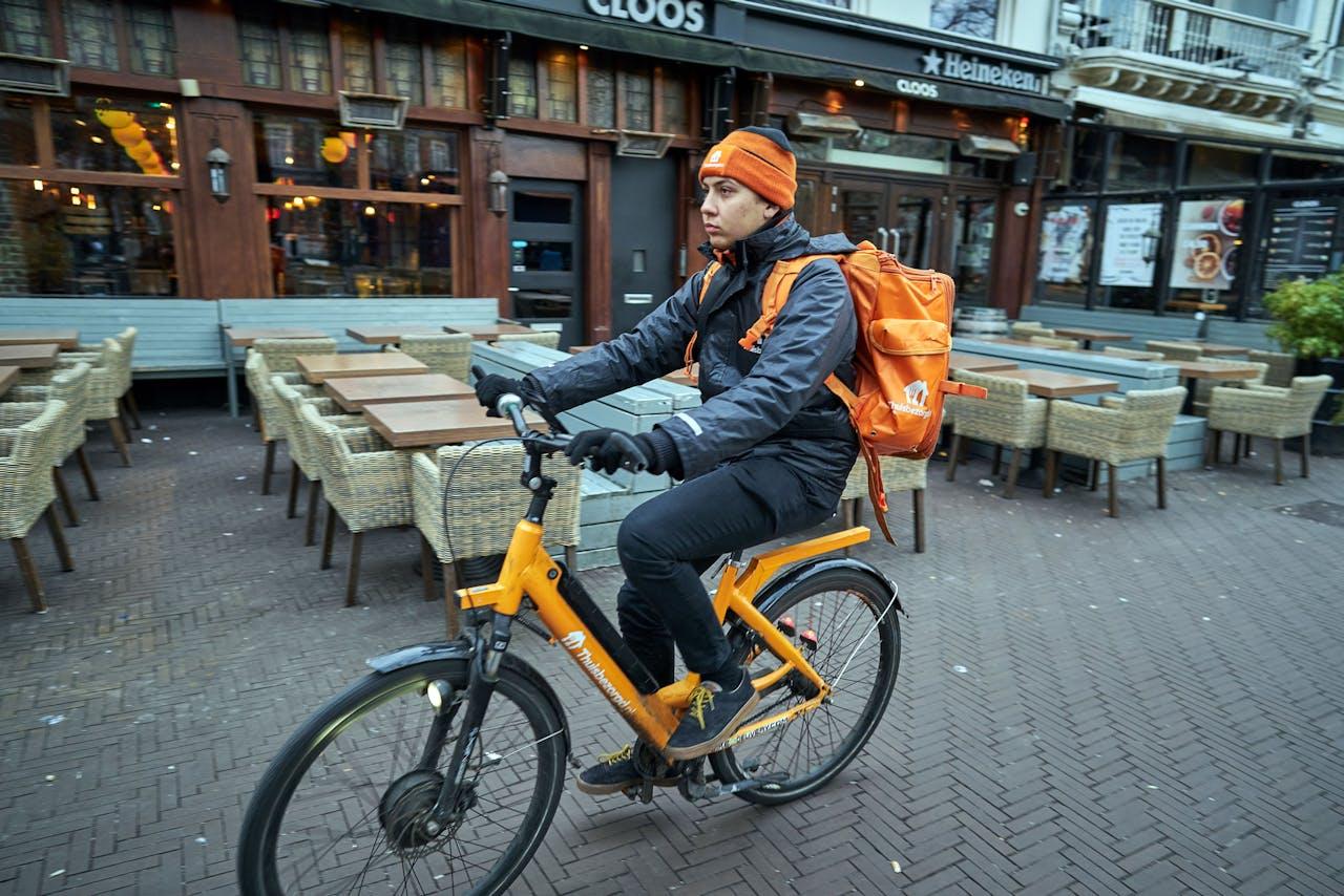 De terrassen op het Plein in Den Haag zijn leeg terwijl een bezorger van thuisbezorgd langs fietst. Het kabinet heeft besloten dat alle horeca drie weken dicht gaan om verspreiding van het coronavirus in te perken. ANP PHIL NIJHUIS
