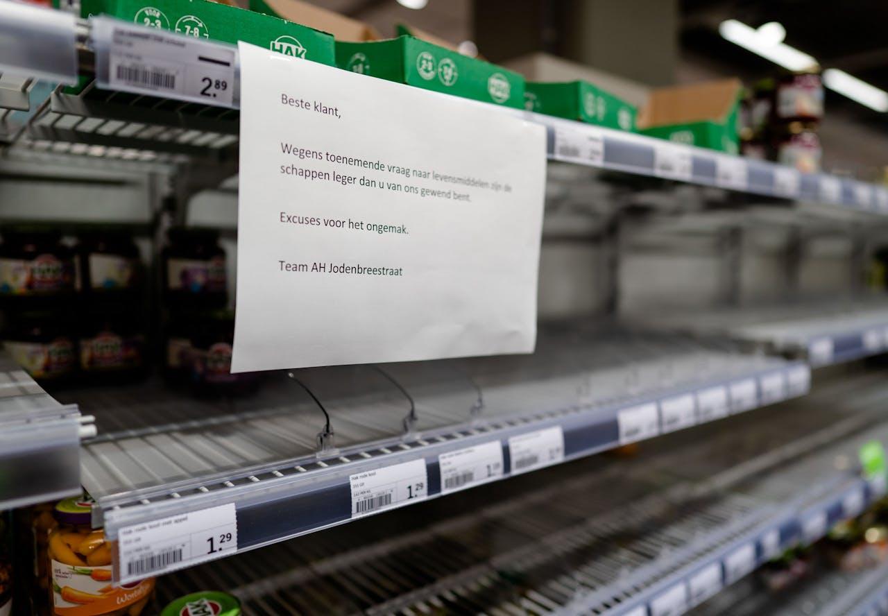 Lege schappen bij een filiaal van Albert Heijn in Amsterdam. De gevolgen van de uitbraak van het coronavirus in Nederland zijn in de supermarkten te merken.