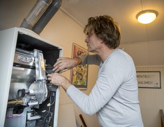 Een onderhoudsmonteur inspecteert een HR-ketel