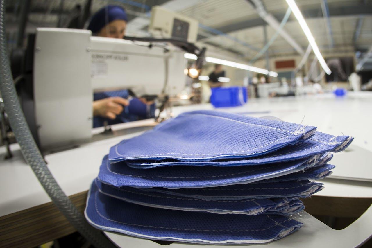Medewerkers bereiden mondkapjes voor in een naaiatelier