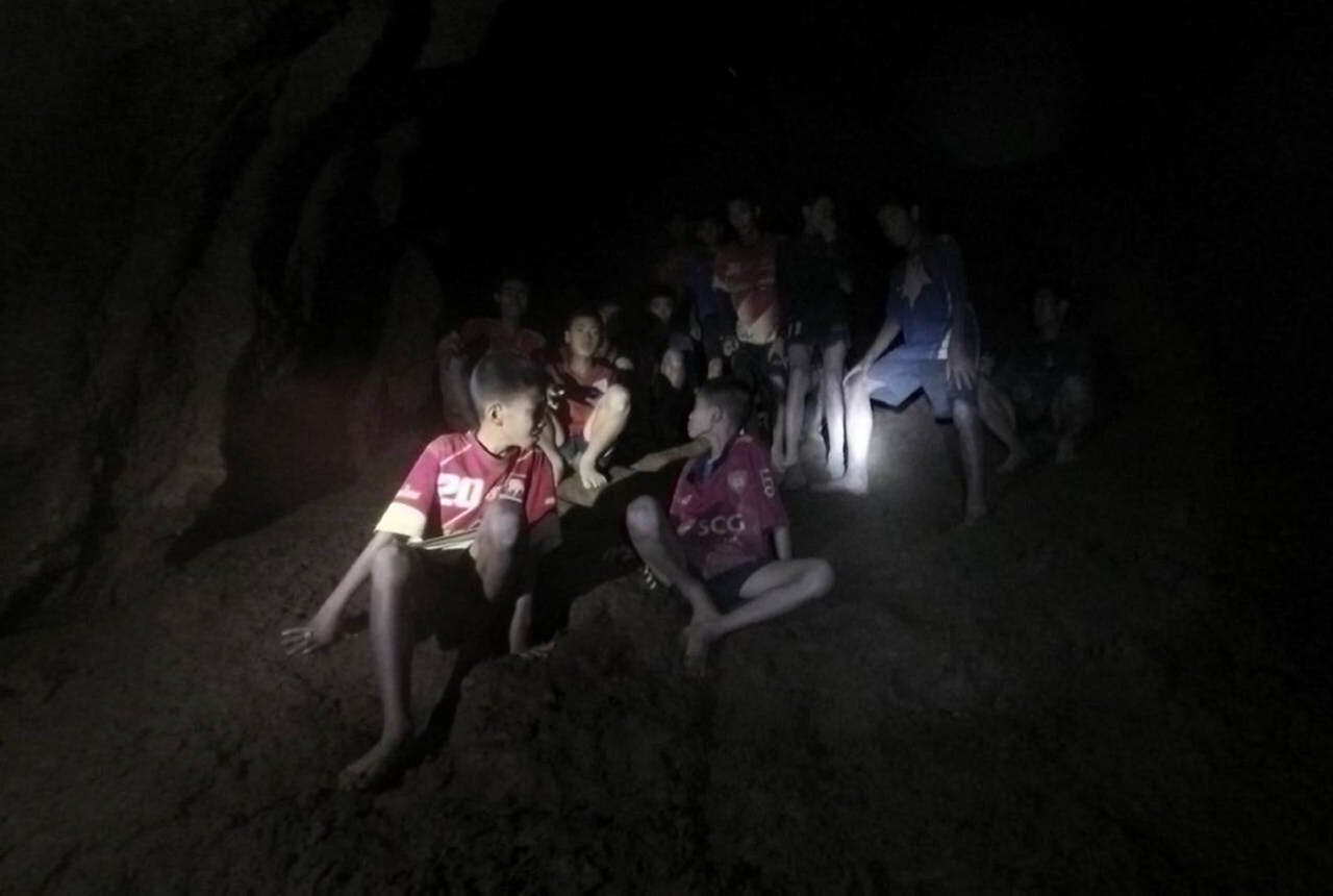 2018-07-02 00:00:00 epaselect epa06859102 An undated handout photo released by Royal Thai Army on 03 July 2018 shows the missing 13 young members of a youth soccer team including their coach, moments they were found inside the cave complex at Tham Luang cave in Khun Nam Nang Non Forest Park, Chiang Rai province, Thailand. Chiang Rai provincial Governor Narongsak Osatanakorn said on 02 July that all of 13 young members of a youth soccer team including their coach have been found alive in the cave. EPA/ROYAL THAI ARMY HANDOUT HANDOUT EDITORIAL USE ONLY/NO SALES