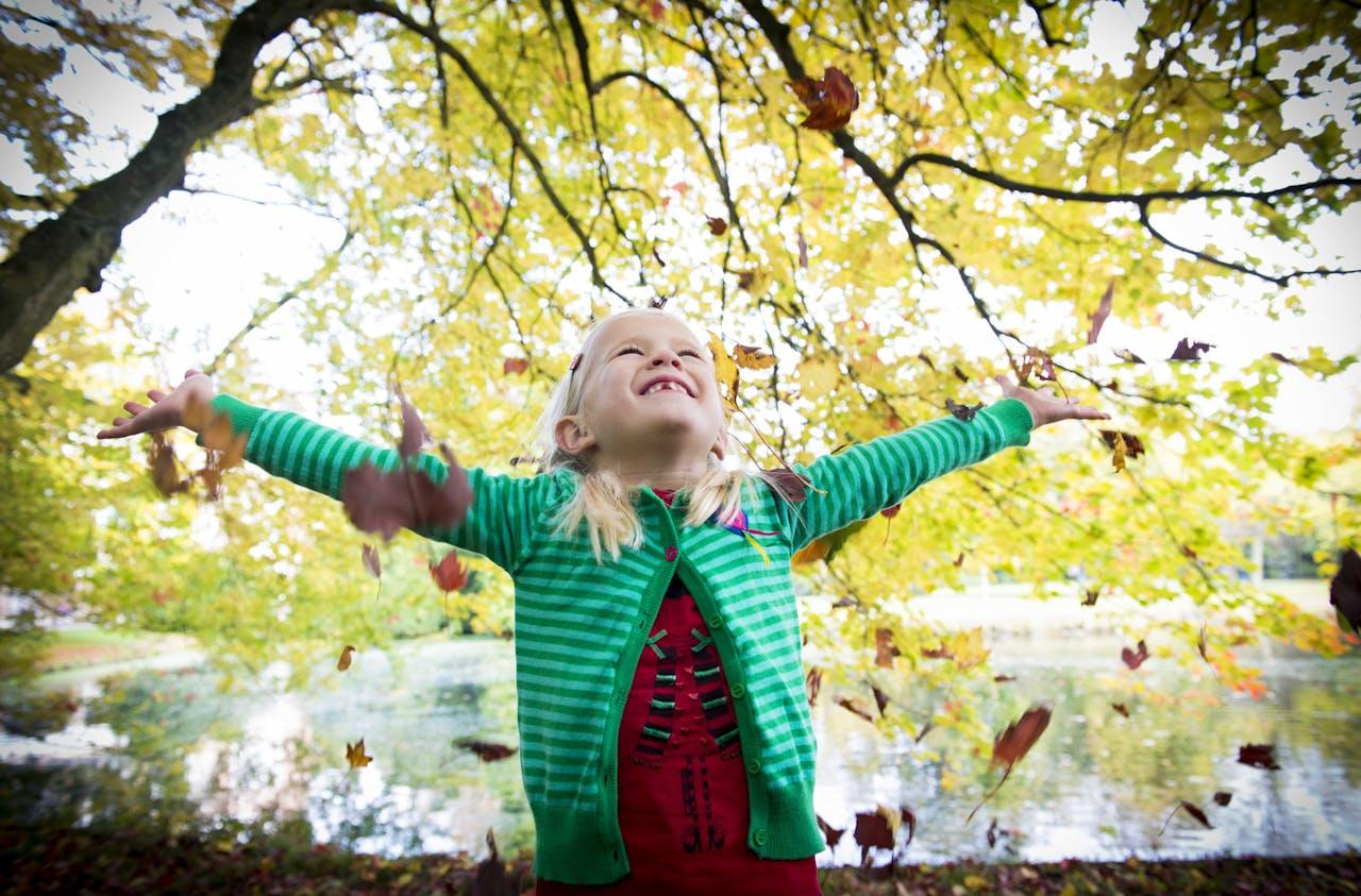 DEN HAAG ILLUSTRATIE - Een meisje gooit herfstbladeren in de lucht. ANP XTRA ROOS KOOLE