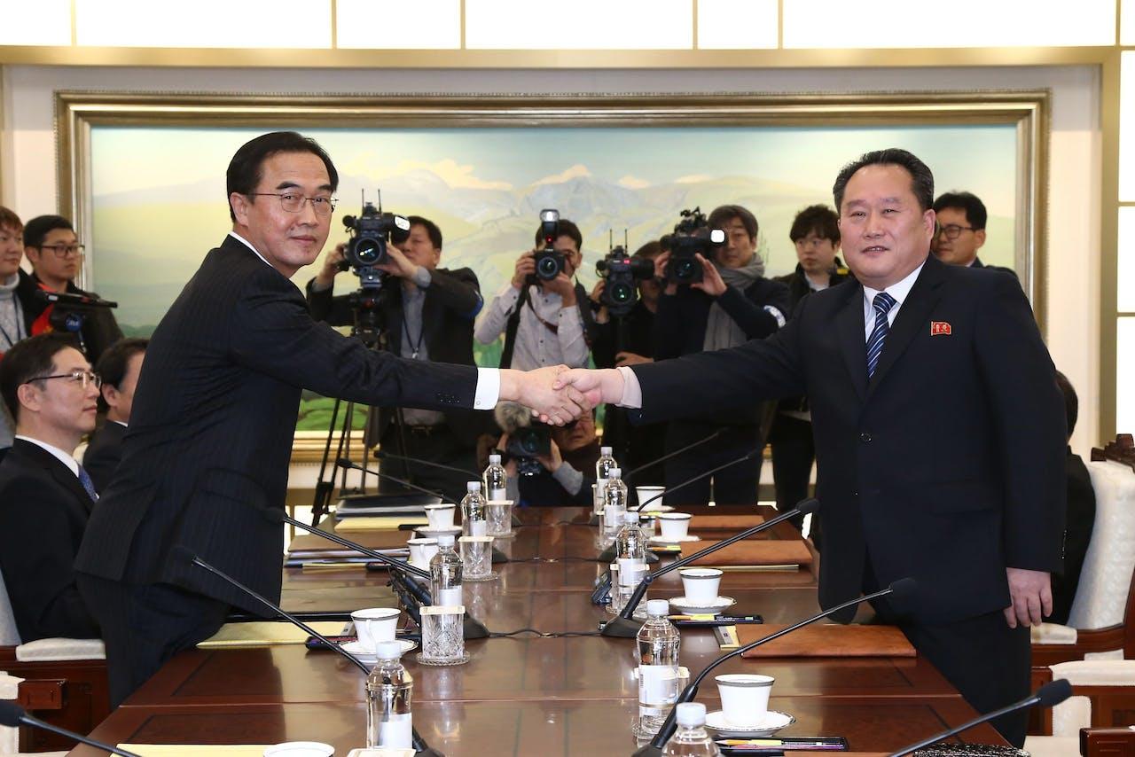De Zuid-Koreaanse onderhandelaar, minister voor Eenwording Cho Myoung-gyon (L) schudt de Noord-Koreaanse onderhandelaar Ri Son-gwon (R) de hand in Panmunjom.