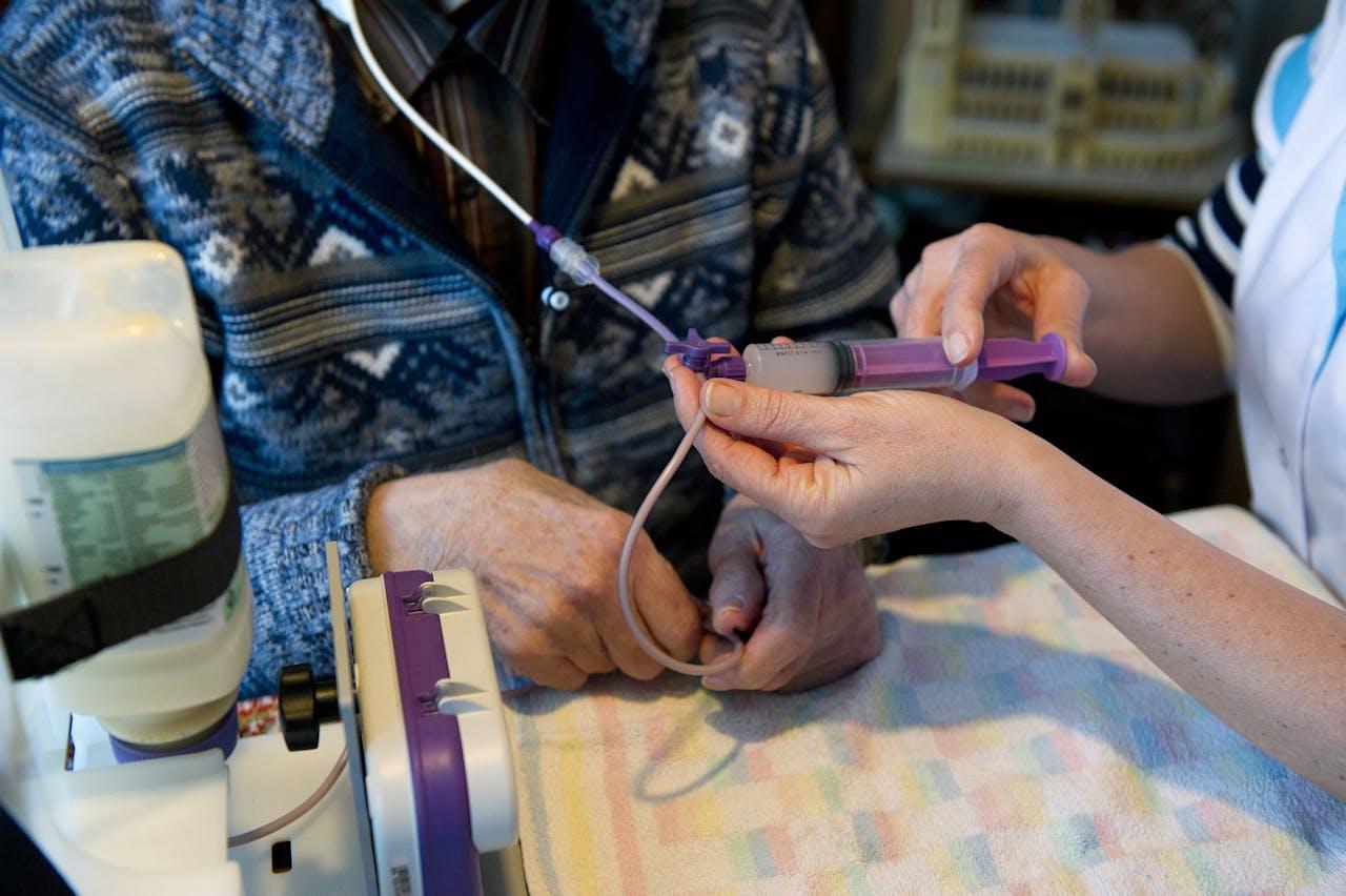Wijkverpleegkundige helpt patiënt met sondevoeding.