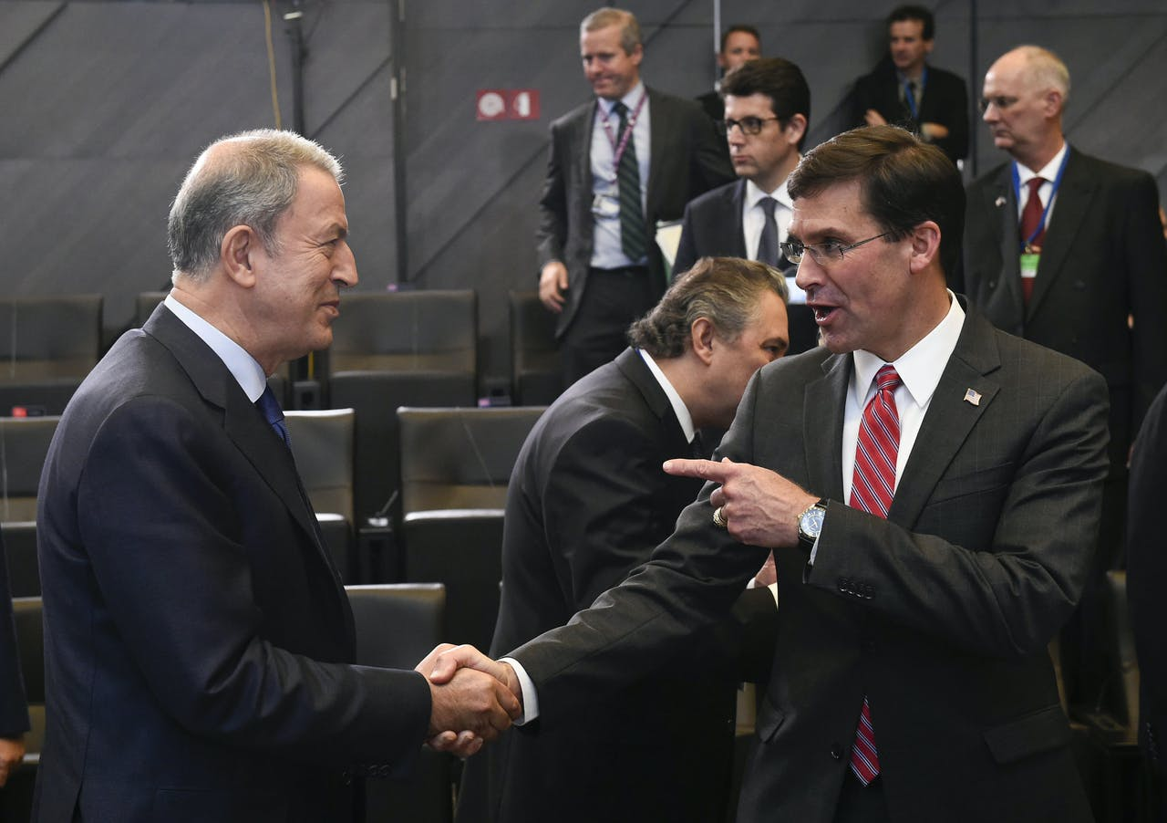 Turks minister van Defensie Hulusi Akar (L) schudt de hand van zijn Amerikaanse collega Mark Esper in het NAVO hoofdkwartier in Brussel tijdens de NAVO Defensie Ministeriële.