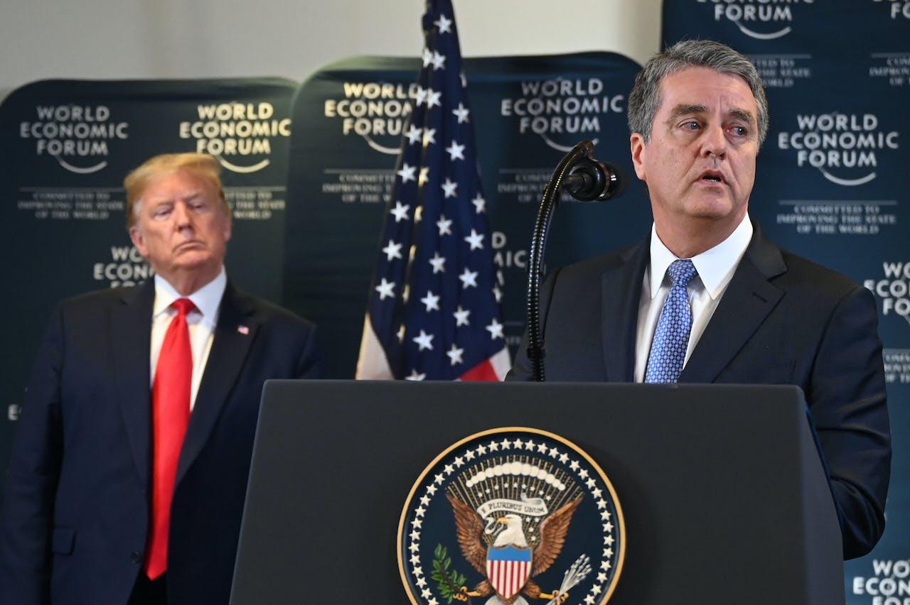 Donald Trump kijkt toe, terwijl WHO-baas Roberto Azevedo een speech geeft, op het World Economic Forum in Davos.