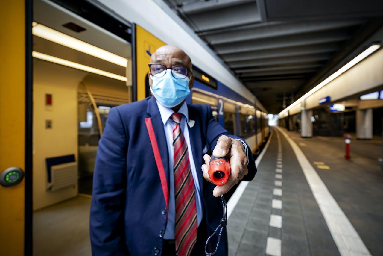 Een conducteur met een elektronische fluit op station Utrecht CS