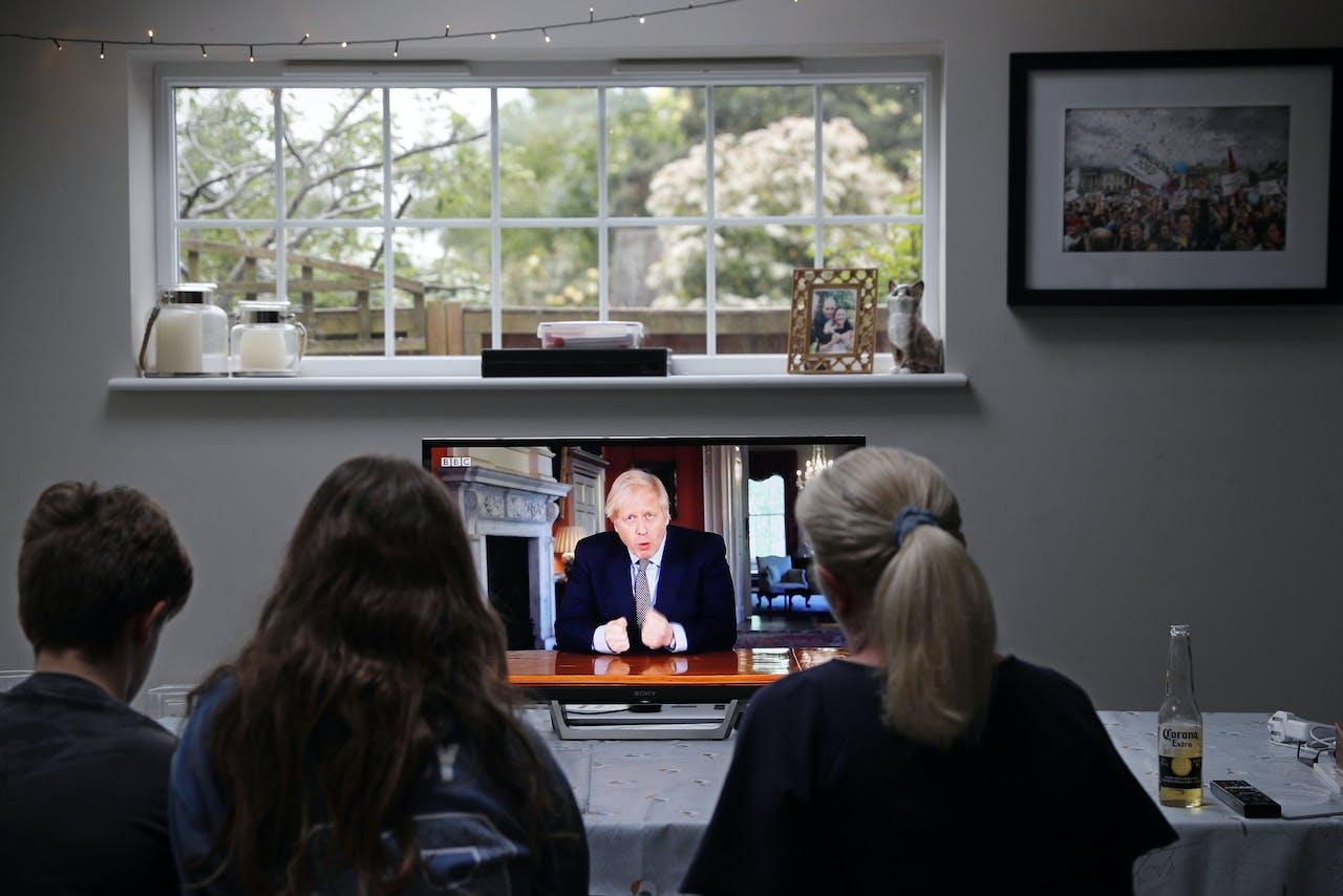 Britten kijken veilig binnen naar de toespraak van Boris Johnson