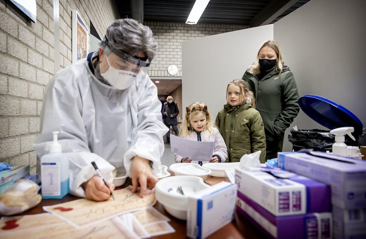 Twee meisjes uit de gemeente Lansingerland krijgen een oorkonde en een knuffel na te zijn getest op het coronavirus.