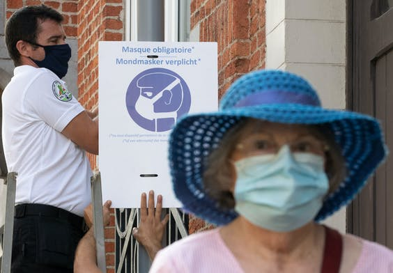 Stadswerkers hangen waarschuwingen om mondkapjes te dragen op in Woluwe-Saint-Lambert in de regio Brussel.
