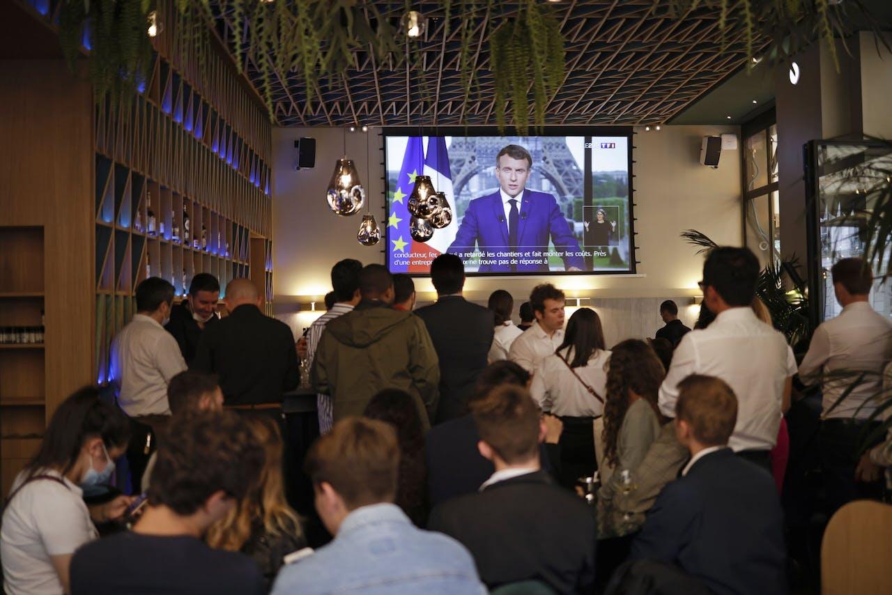 Barbezoekers aanschouwen de toespraak van Macron, waarin hij aankondigt dat het land een verplichte gezondheidsverklaring gaat invoeren.