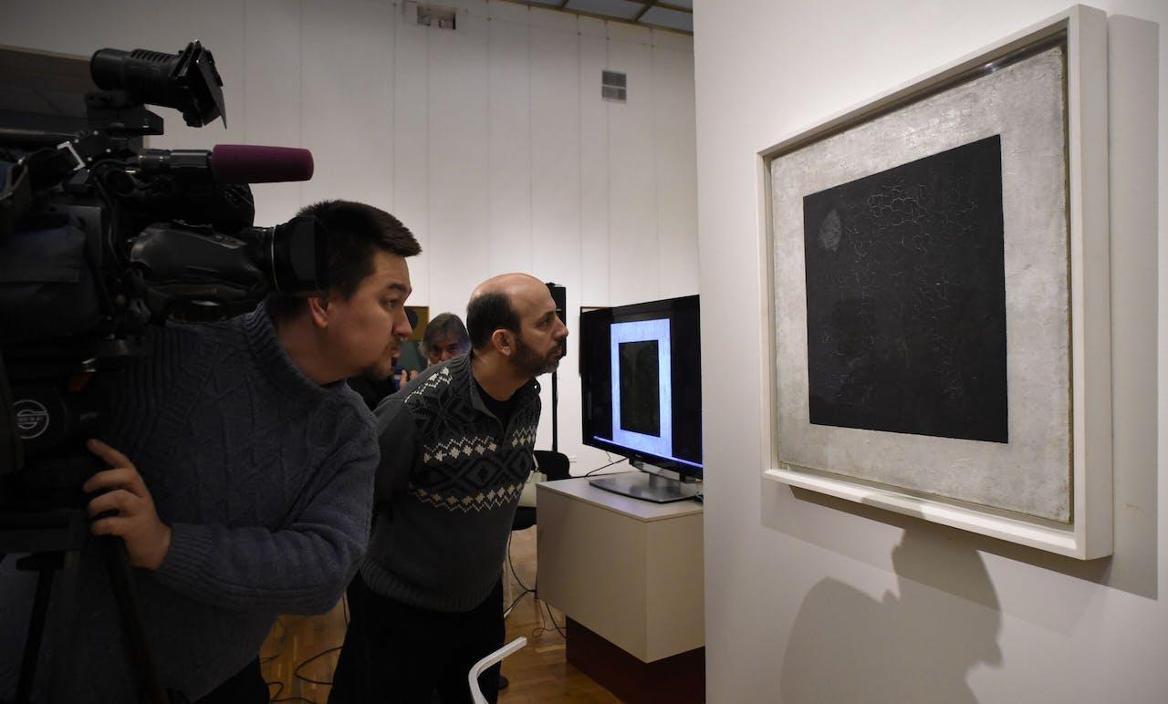 Journalisten kijken naar het zwarte vierkant, in de Tretjakov-gallerij in Moskou.