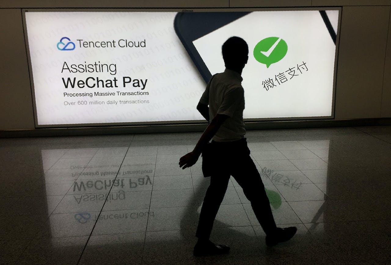 Een man loopt voorbij een advertentie van het social media-platform 'WeChat', van het Chinese bedrijf Tencent in Hong Kong.