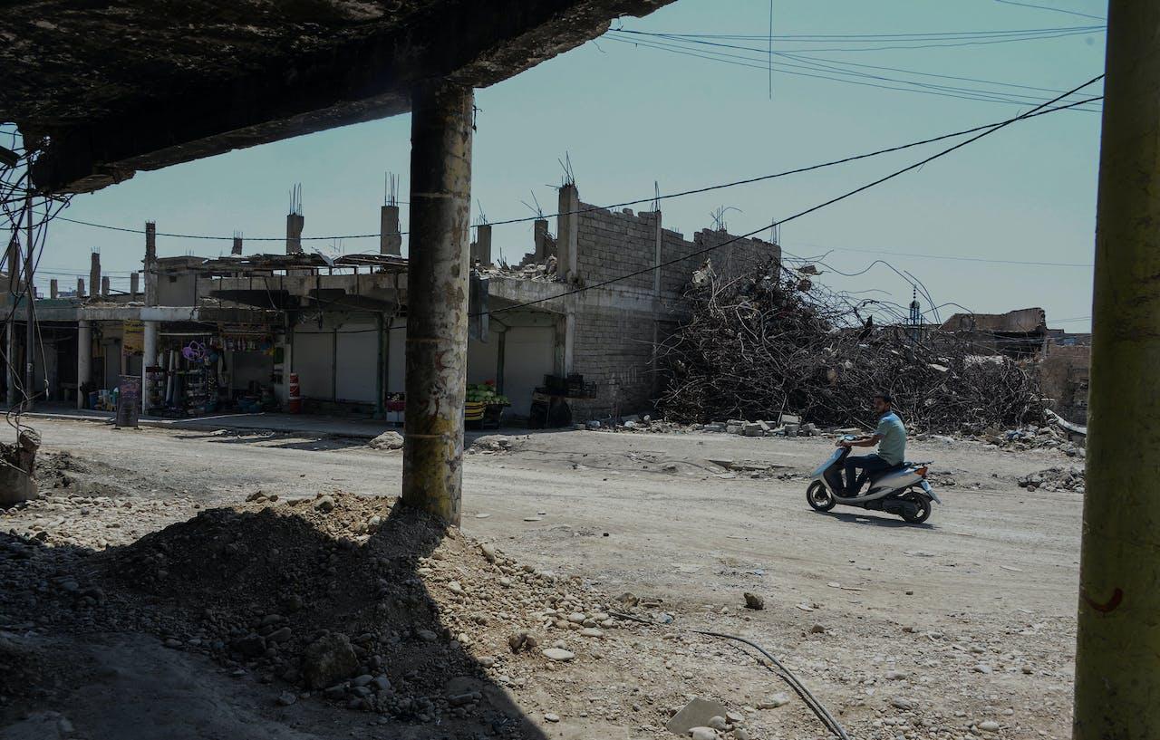 Een man in de zwaar beschadigde straten van Mosul
