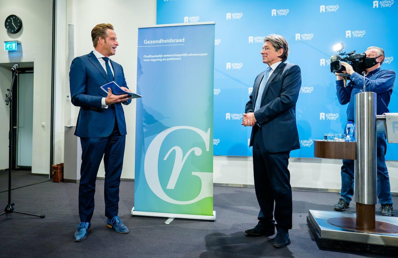 Minister Hugo de Jonge neemt het voorlopig advies van de Gezondheidsraad over coronavaccins in ontvangst uit handen van Bart-Jan Kullberg, voorzitter van de Gezondheidsraad.