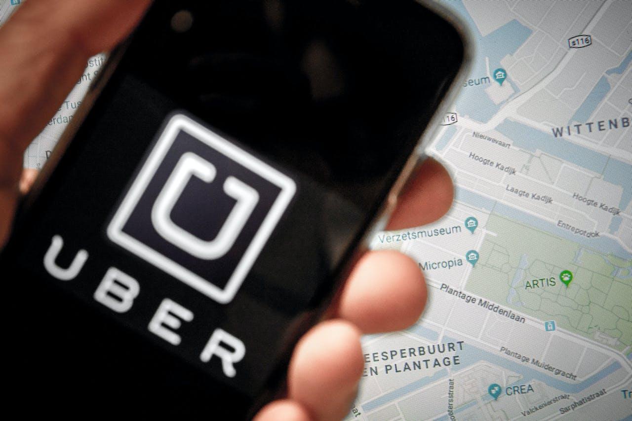 Een telefoon met het Uber logo voor een map van Amsterdam.