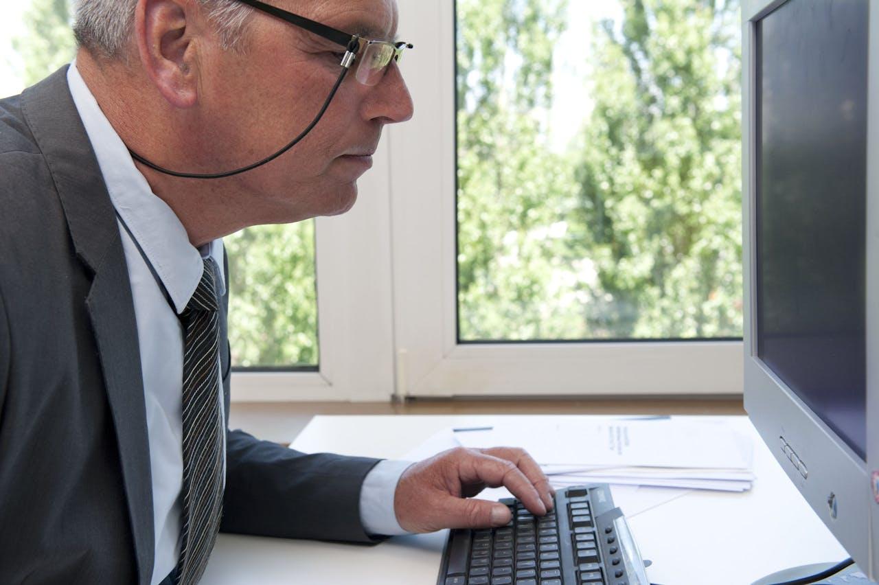 ILLUSTRATIE - Oudere man aan het werk op kantoor. ANP XTRA ROOS KOOLE