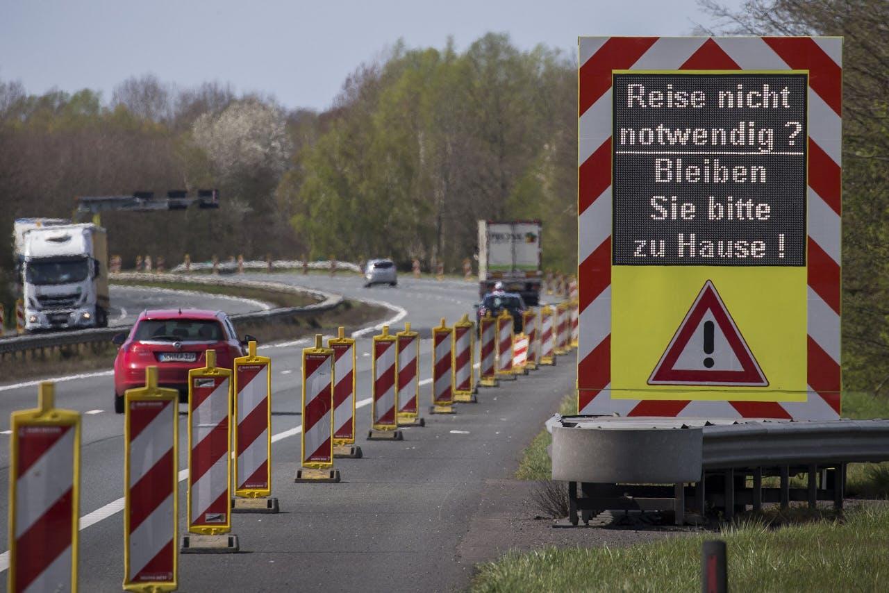 Een Informatiebord met oproep om thuis te blijven langs de snelweg A-1 bij de Duitse grens. De Marechaussee voert extra controles uit aan de grens met Duitsland. Om verdere verspreiding van het coronavirus te voorkomen, ontmoedigt de marechaussee mensen die de grens over willen, maar daarvoor geen dringende reden hebben.