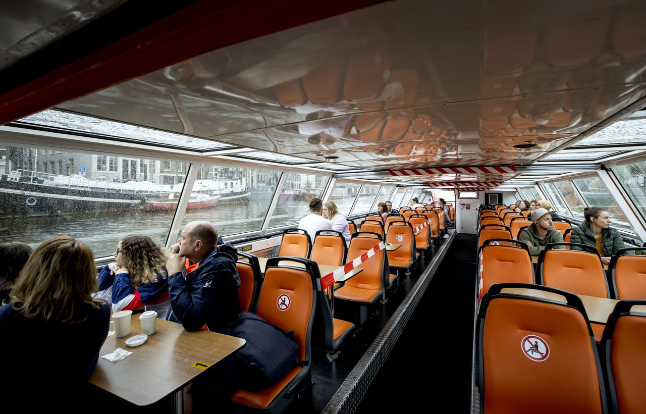 Toeristen maken een rondvaart door de Amsterdamse grachten.