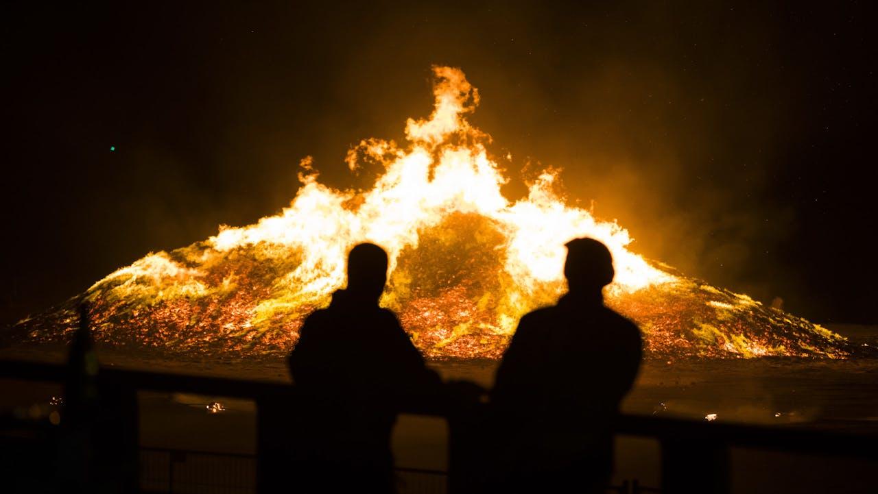 Twee mensen kijken naar het vreugdevuur in Scheveningen