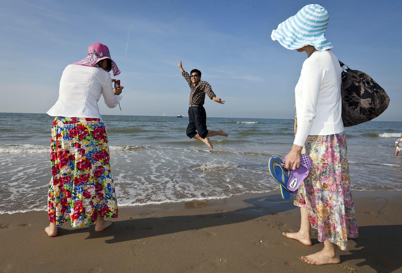 Chinese toeristen genieten van het mooie weer op het strand in Scheveningen