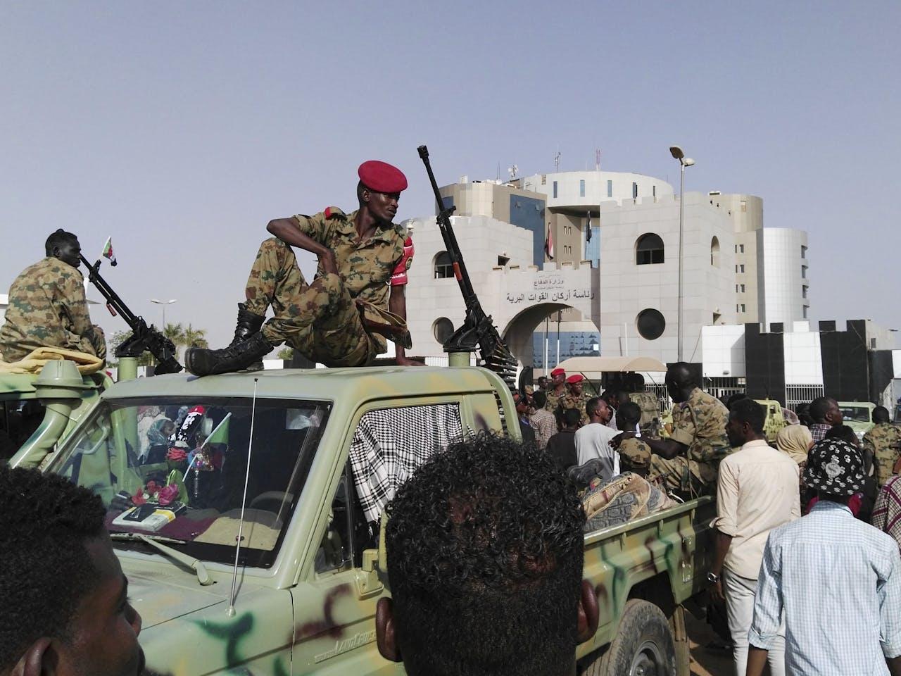 Soedanese soldaten kijken hoe een menigte zich verzamelt in een straat in Khartoem, de hoofdstad van Soedan.