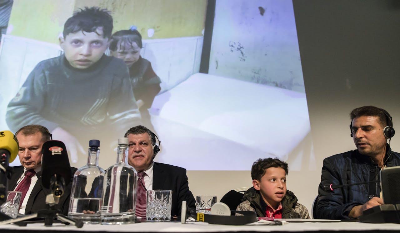De Russische ambassadeur in Nederland Aleksander Sjoelgin, dr Ghassan Obeid en het Syrisch jongetje Hasan tijdens een persconferentie na afloop van OPCW-beraad over gebruik van gifgas in Syrie. Rusland ontkent het gebruik ervan en zegt dat getuigen liegen in geënsceneerde video's.