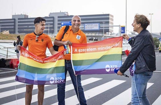 KRO-NCRV-presentator Klaas van Kruistum deelde op Schiphol regenboogvlaggen uit aan voetbalsupporters die naar de wedstrijd in Hongarije gingen.