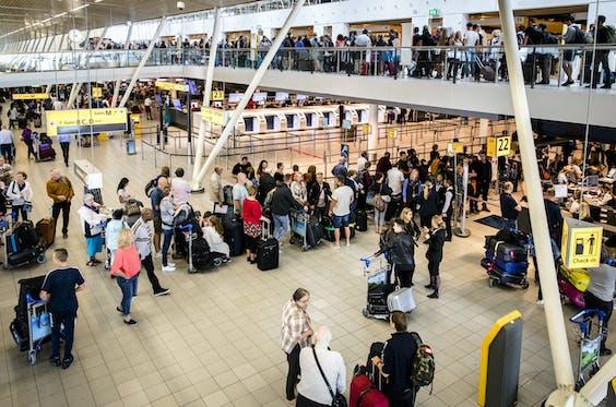 Reizigers in de vertrekhal van Schiphol op de drukste dag van het jaar voor de luchthaven.
