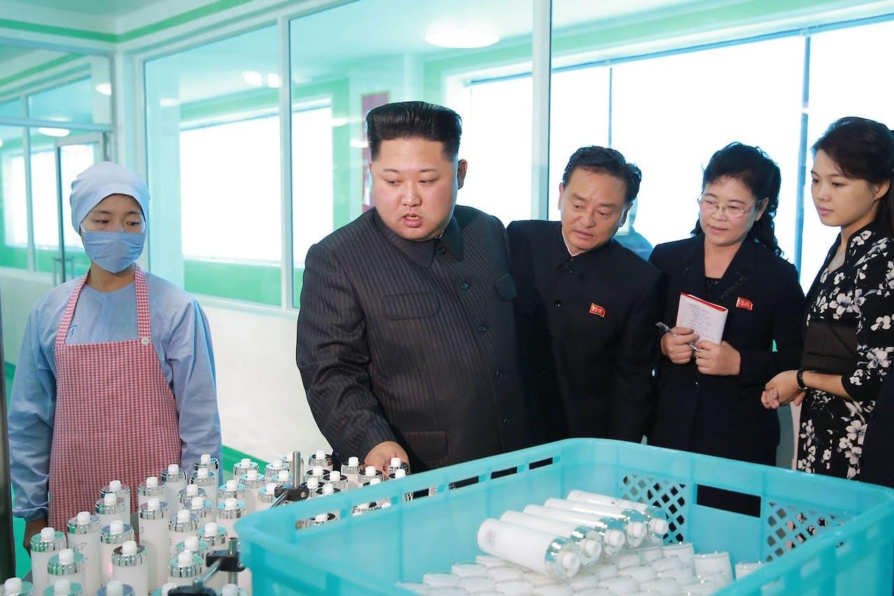 Het bezoek aan de cosmeticafabriek. Rechts, in het zwart met witte bloemen, de echtgenote van de Leider.
