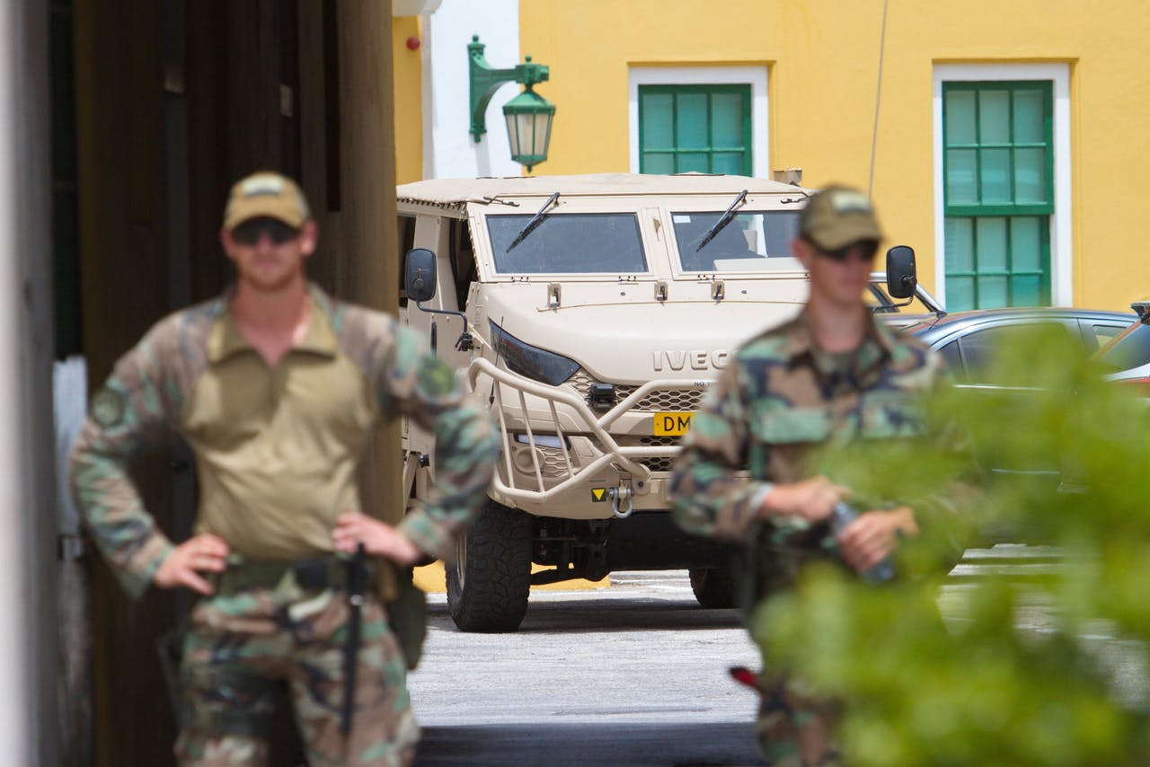 Nederlandse militairen staan wacht bij het het regeringsgebouw Fort Amsterdam.