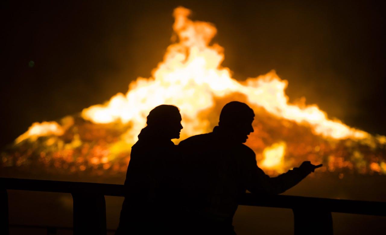 Twee mensen kijken naar het vreugdevuur.
