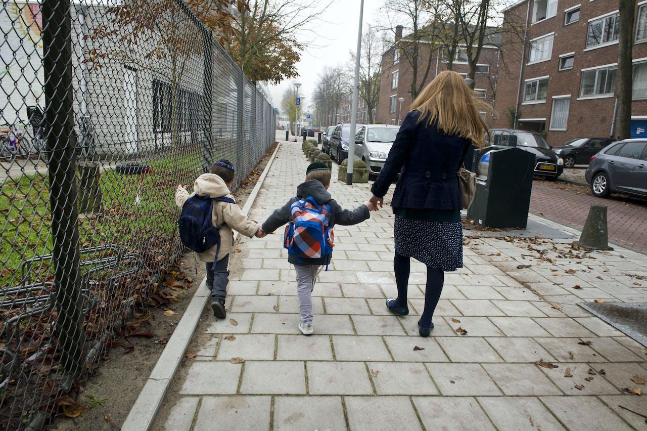Een moeder met haar kinderen op weg naar huis