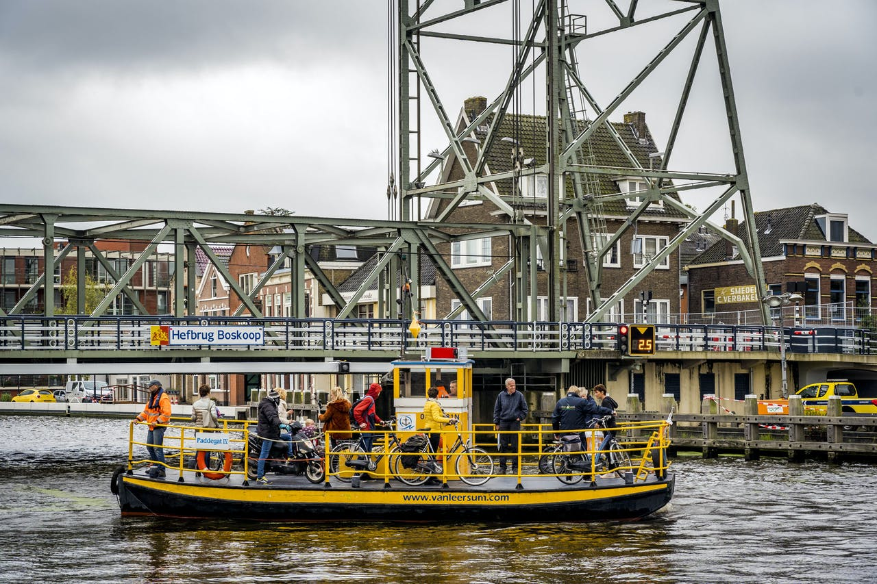 Fietsers worden met een pontje overgezet, nu de hefbrug in Boskoop is gesloten. Bij een controle bleek dat de constructie van de brug onveilig is.