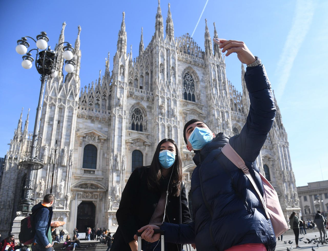 Toeristen nemen een selfie voor de kathedraal van Milaan