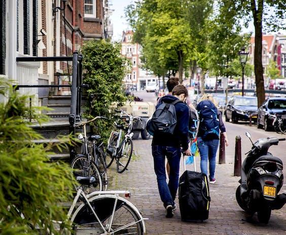 Toeristen met rolkoffers op de grachten in Amsterdam.