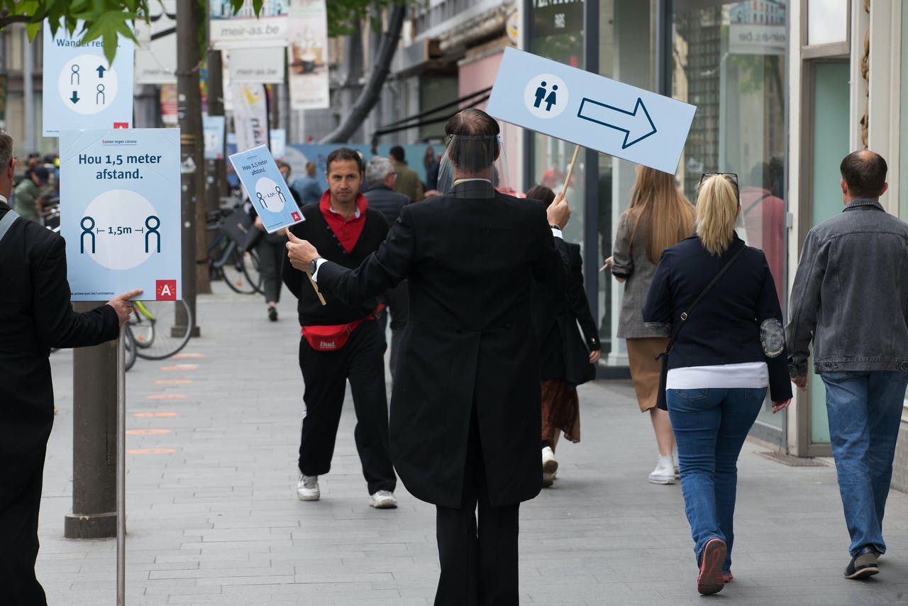 2020-05-16 02:00:00 People hold placards during an action to explain social distancing rules at the Meir shopping street in the city centre of Antwerp on May 16, 2020, as Belgium eases lockdown measures taken to curb the spread of the COVID-19 pandemic, caused by the novel coronavirus. NICOLAS MAETERLINCK / BELGA / AFP