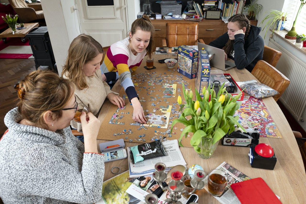 2020-03-19 13:40:03 SASSENHEIM - Leden van een gezin puzzelen aan de eettafel om de tijd te verdrijven. De overheid adviseert mensen zoveel mogelijk binnen te blijven vanwege het coronavirus. ANP FRANK VAN BEEK