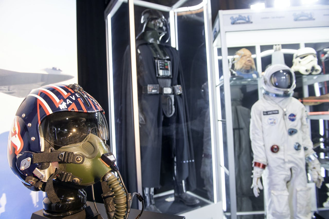 """2020-08-26 17:47:39 (From L) Pete """"Maverick"""" Mitchell's (played by Tom Cruise) fighter pilot helmet from """"Top Gun"""" (1986), 1977/1978 Darth Vader Promotional Costume with Poster-Matched Helmet from the film """"Star Wars: A New Hope"""" (1977), and Neil Armstrong's Screen-Matched Gemini Spacesuit (worn by actor Ryan Gosling) from """"First Man"""" (2018) are seen at Prop Store, August 26, 2020, in Valencia, California. The pieces are part of the over 850 film and TV props offered to the bidders during one of the world's largest live auctions of film and TV memorabilia organized by Prop Store. The sale of hundreds of legendary Hollywood movie props will be live-streamed on August 26-27, including items wielded by Indiana Jones and Clint Eastwood's Western outlaw Josey Wales. VALERIE MACON / AFP"""