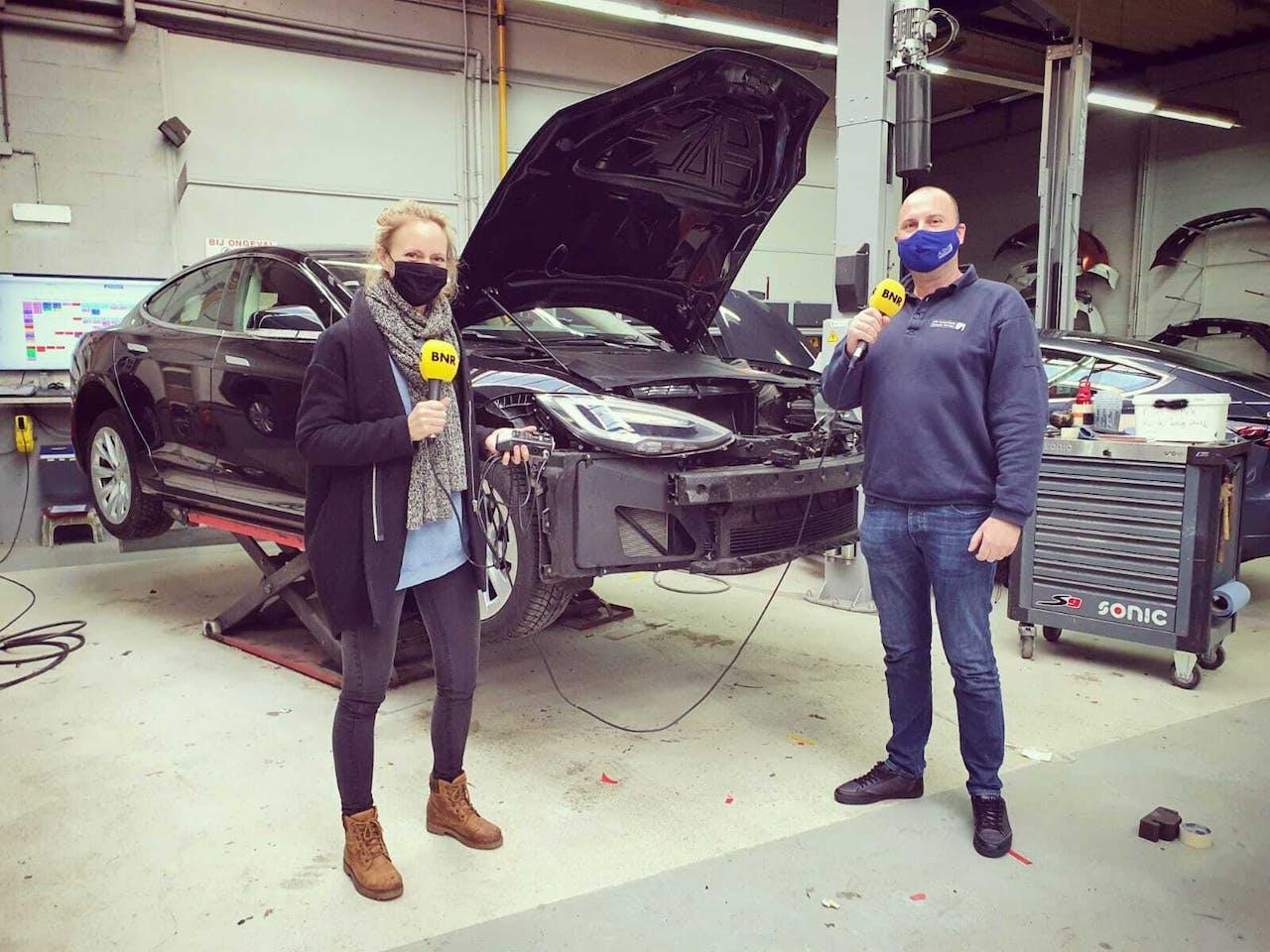 Dennis Petrus, directeur van ASN Autoschade Vermaire Haarlem, laat Karlijn Meinders zien hoe je schade aan een Tesla kunt repareren.
