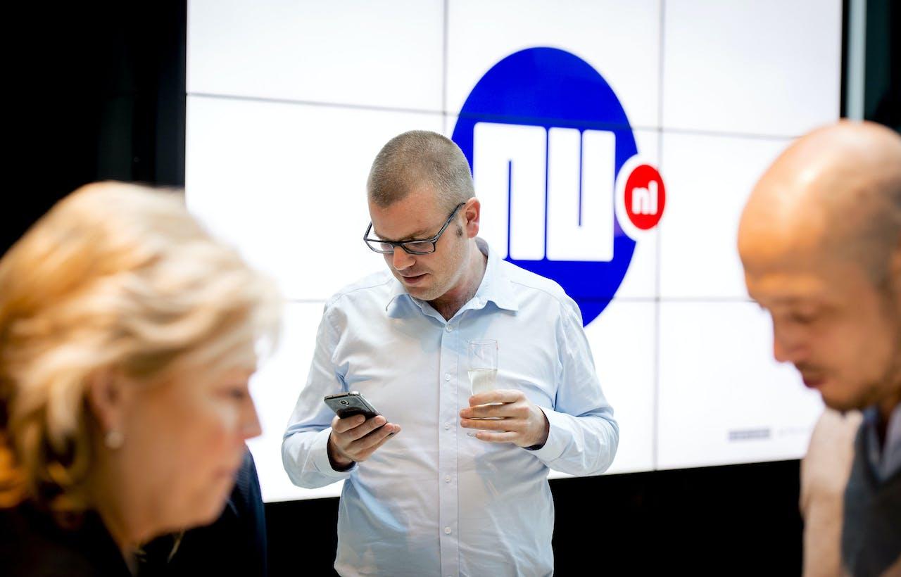 Hoofdredacteur Gert-Jaap Hoekman bekijkt de nieuwe app op zijn telefoon na de lancering van de vernieuwde NU.nl site.