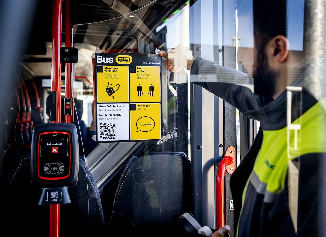 Een medewerker van Connexxion hangt een poster met coronamaatregelen op in een bus.