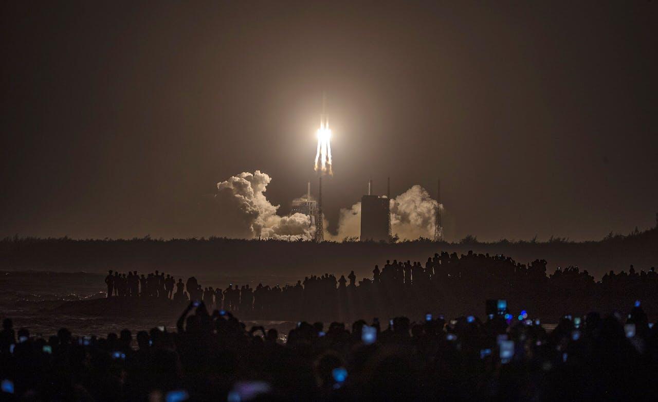 Een mensenmenigte kijkt hoe de Chinese Chang'e-5 opstijgt in China voor een maanmissie om maanstenen op te halen.