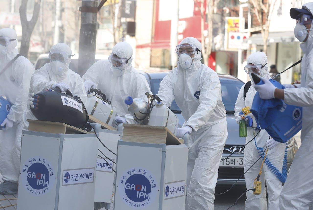 Er wordt met desinfecterende spray gespoten op straat in Seoul, Zuid-Korea. In dat land kwamen al 13 mensen om het leven doordat zij besmet raakten met het coronavirus